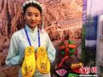 7月21日,甘肃800余种特色农牧产品纷纷亮相中国石化甘肃特色农牧产品订货会。图为身着民族服饰的东乡族少女展示手工刺绣产品。 史静静 摄 - 甘肃新闻