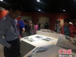 图为来自海内外的专家、学者驻足参观展览。 冯志军 摄 - 甘肃新闻