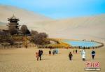 资料图:游客在国际旅游名城甘肃敦煌参观。图为敦煌月牙泉畔游人不绝。王斌银 摄 - 甘肃新闻