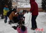 瓦天沟小学老师仿佛回到自己的孩童时光,图为老师和小学生们在课间痛痛快快得玩雪。 敬斐斐 摄 - 甘肃新闻
