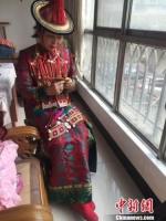 资料图:甘肃裕固族文化传承人瑙尔姬斯在家中绣制裕固族服饰。 杨娜 摄 - 甘肃新闻