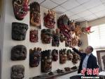 图为贾森栋和他收藏的傩面具。 刘薛梅 摄 - 甘肃新闻