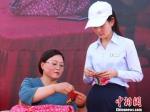 """4月19日,在甘肃庆阳市举办的""""小崆峒旅游文化节""""上,当地民间手工艺传承人在向游客教授剪纸技艺。 陈飞 摄 - 甘肃新闻"""