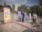 图为民众驻足观看禁赌成果展和禁赌宣传图片。崔琳 摄 - 甘肃新闻