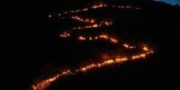 """6月14日至18日,第三届陇南文县白马人·民俗文化旅游节举行。图为火把星星点点从山顶奔腾而下,顺着蜿蜒山路呈现""""S""""形。 杨艳敏 摄 - 甘肃新闻"""