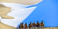 图为11月15日,游客在雪后的甘肃敦煌鸣沙山月牙泉景区欣赏大漠雪景。 王斌银 摄 - 甘肃新闻