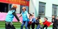 图为志愿者们和树屏镇镇中心幼儿园的孩子们做游戏。 崔琳 摄 - 甘肃新闻