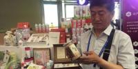 图为兰州一农业科技公司总经理梁建民手拿瓶装藜麦向驻足于展台前的客商们介绍产品。 - 甘肃新闻