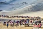 2019年7月18日,中外游客在敦煌鸣沙山月牙泉景区骑骆驼观光游览,形成近2公里长的宛如长龙的观光驼队。(资料图) 王斌银 摄 - 甘肃新闻