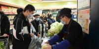 2月11日下午,甘肃兰州市民在超市内挑选完蔬菜后排队称重。(王文嘉 摄) - 人民网