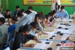 图为实践团成员教孩子们写毛笔字。 王玉丰 摄 - 甘肃新闻